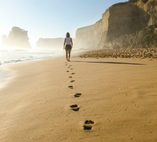 woman's footsteps walking on the beach